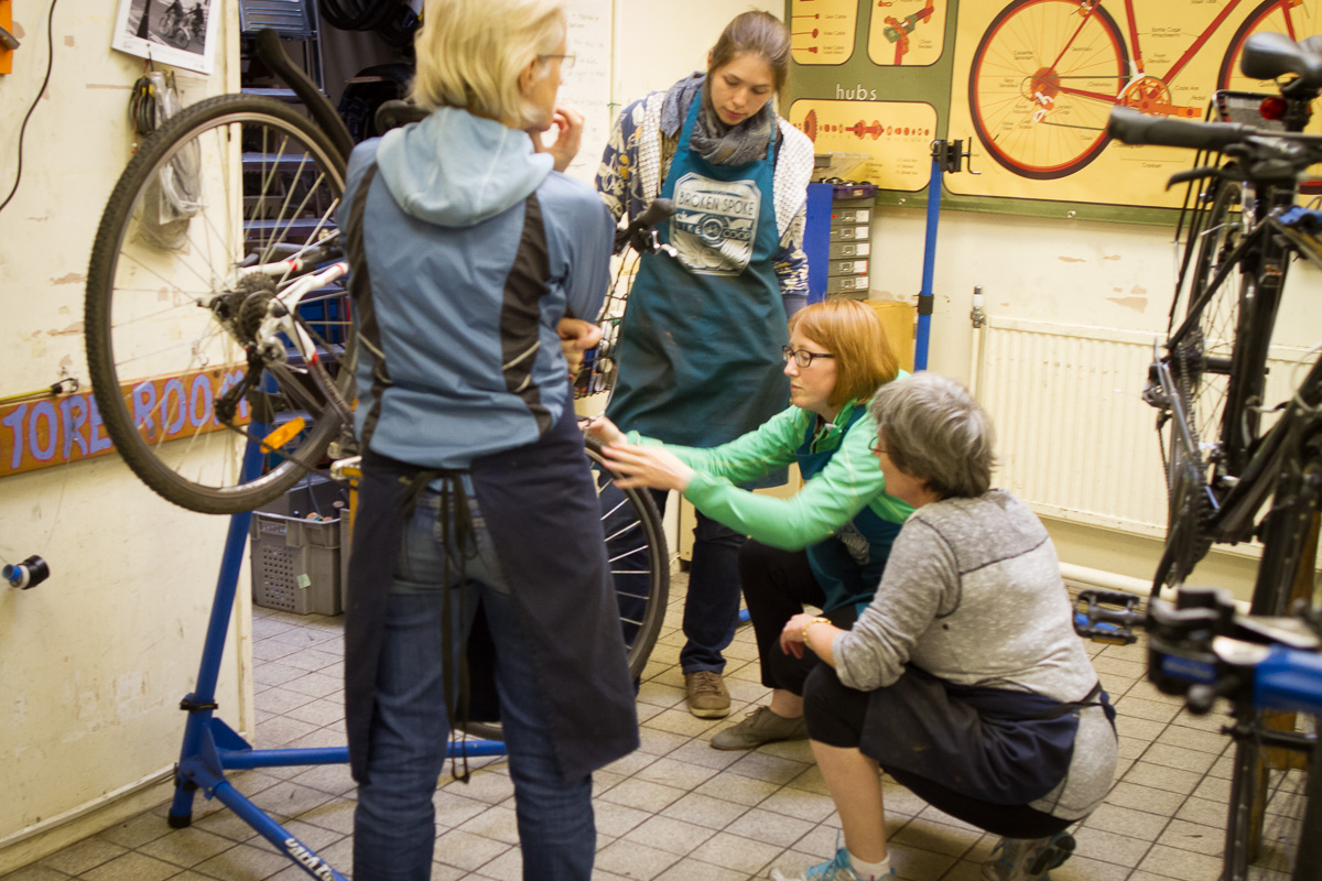 Calista showing Beryl's Night participants how to adjust brakes